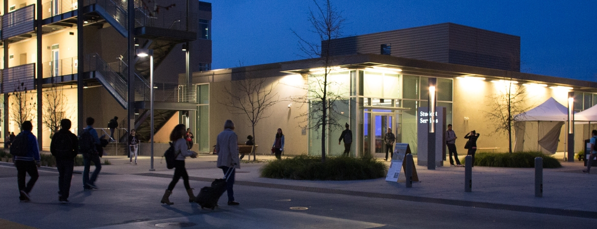 The Student Services Building at night with people crossing the street.  The Math Center is located inside the SSB.